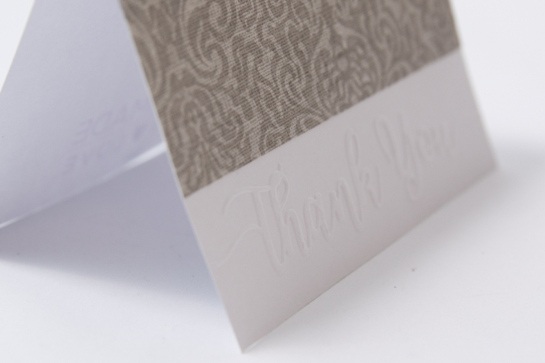 white card with silver wallpaper on top of the words thank you embossed